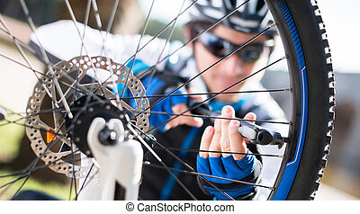 Male Cyclist Inflating Tire Of Bicycle; Outdoors