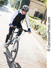 Young Man Cycling - Portrait Of Young Man Cycling; Outdoors