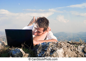 Wireless communication - Young man using his laptop, lying...