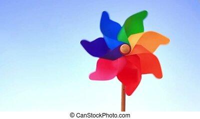 Colorful pinwheel toy - Spinning pinwheel toy against blue...
