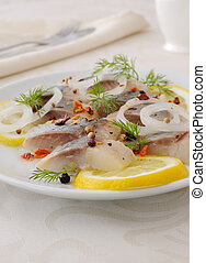 Slices of salted herring with onion, lemon and spices -...
