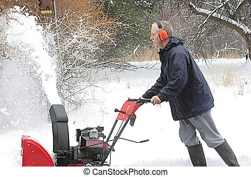 Man Using A Snow Blower In Winter