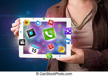 Lady holding a tablet with modern colorful apps and icons -...