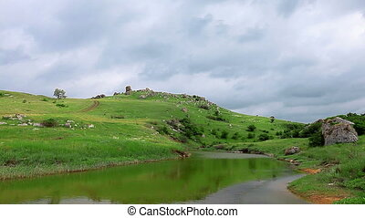 green hills - mountain river in the background of green...