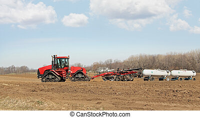 Plowing and Fertilizing - Tractor pulling plow and anhydrous...