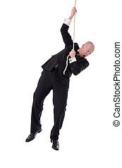 businessman hanging on rope - Businessman hanging onto a...