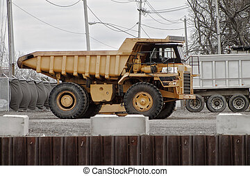 Big Yellow Dumptruck - A big-wheeled construction truck sits...