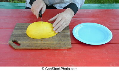 cutting yellow melon on table - cutting yellow fresh melon...