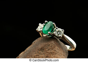 White gold ring with diamonds and emerald stone
