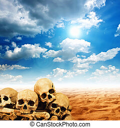 Human skulls in desert land with clouds over a blue sky.