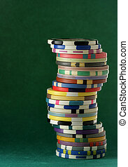 Stack of colorful casino chips over green background