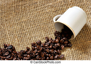 Coffee cup and coffee beans over burlap background