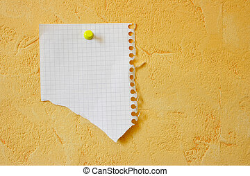 Lacerated blank sheet attached to a yellow wall