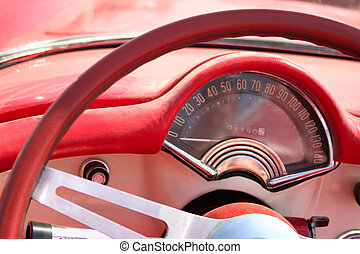 Speedometer and wheel of classic red car cloose-up