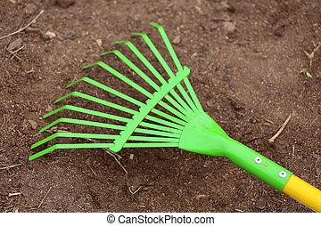 Rake - A close up view of a metal green and yellow yard rake