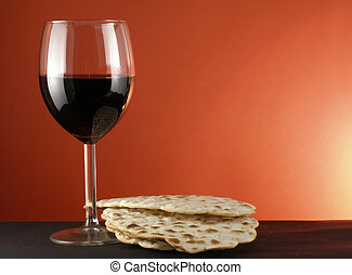 Wine and matzoh - Glass of wine and matzoh over red...