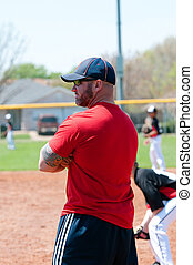 Baseball coach at first base line looking at batter