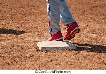 Baseball teen on base - Lower body shot of a teen baseball...
