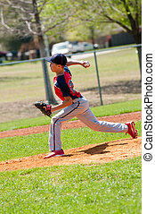 Teen baseball pitcher in the middle of throw