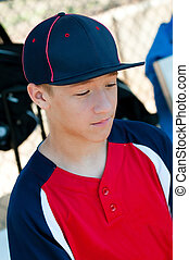 Teen Baseball boy in dugout - Teen baseball player looking...