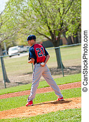 Teen baseball pitcher looking at the batter.