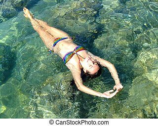 Young woman in bikini floating in clear shallow water