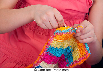 little girl knitting with a hook