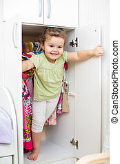 kid girl playing ang hiding inside wardrobe