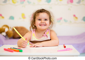 little smiling child drawing with felt-tip pen