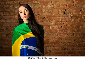 woman in the Brazilian flag on the background of a brick...