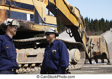 bulldozer and workers in action - giant bulldozer with two...