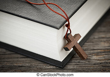 Cross and Bible - Closeup of wooden Christian cross necklace...