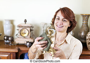 Woman polishing antiques - Happy caucasian woman proudly...