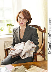 Female interior designer with fabric samples sitting at desk