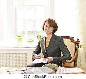 Female interior designer with color samples sitting at desk