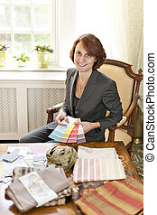 Female interior designer with color samples sitting at desk
