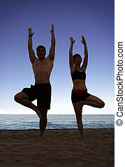 Beach yoga - Couple doing yoga exercise on the beach