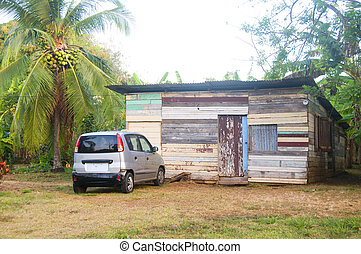 typical native Nicaraguan wood clapboard house with taxi in...