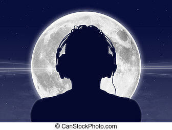 man listening to the music at the full moon - silhouette of...