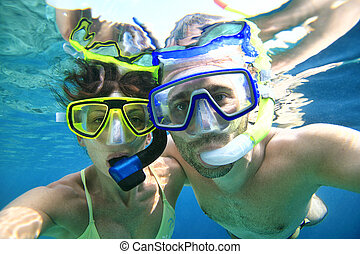 Couple snorkeler in ocean - Woman and man doing snorkeling...