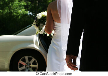 Bride and Groom walking to Limo with flowers