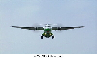 turbo prop plane fly over - green white turbo prop plane fly...