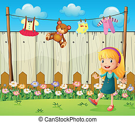 A backyard with hanging clothes and a young girl