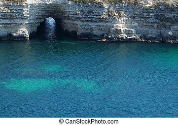 grotto in rock on blue sea