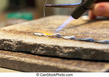 hands of jeweller at work silver soldering Goldsmith working...