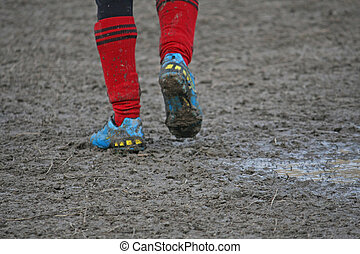 muddy soccer shoes of a child player during a football match...