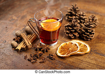 mulled wine with orange and spices on wooden background