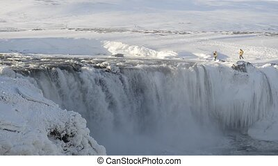 Godafoss in Winter with people exploring the edges of the...