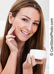 Young Woman Applying Cream - Attractive Young Woman Applying...