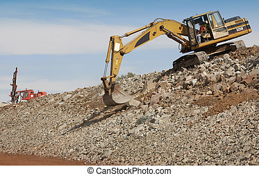 Excavator and drill machine. - Excavator unloading sand at...